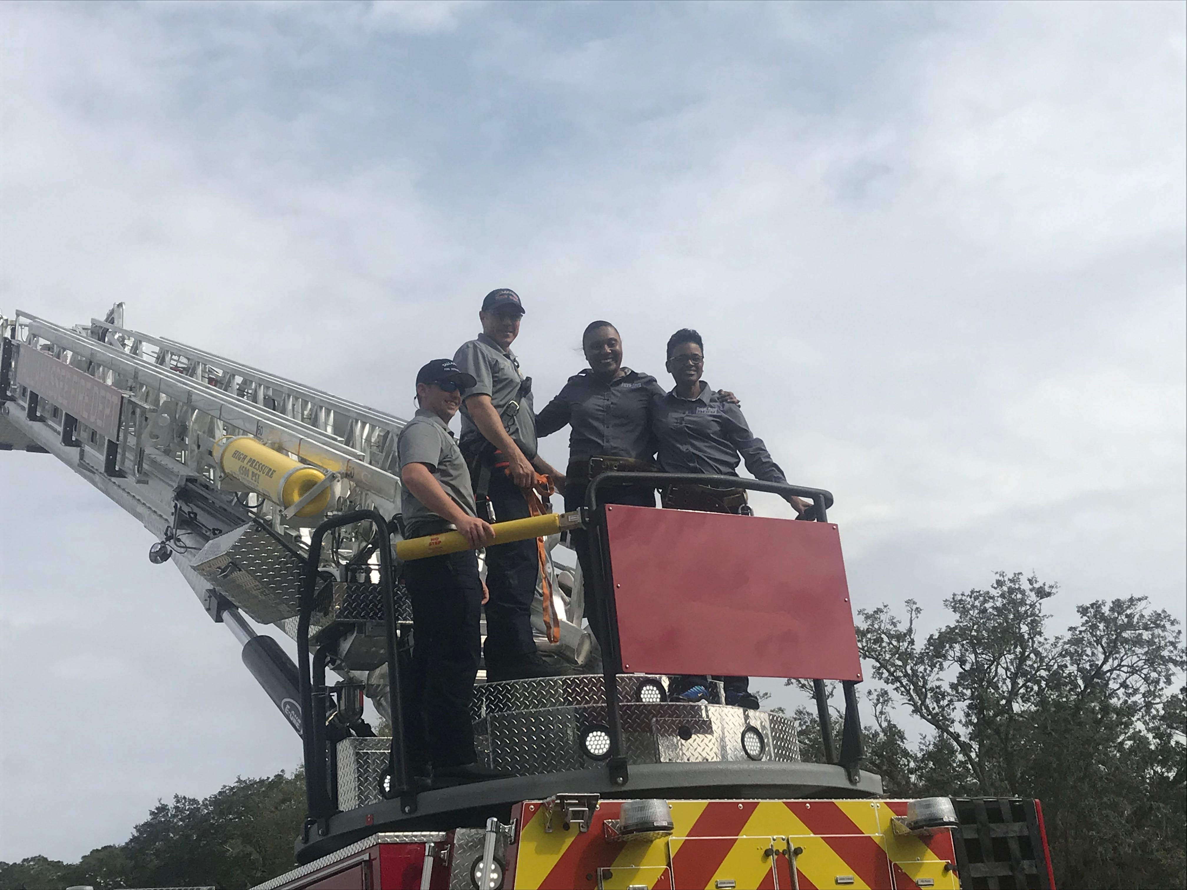 (From left to right) Engineer Jeff Brady, firefighter Tom Burns and Sabal Palm Elementary Principal Anicia Robinson and Jameeka Wallace stand on top of a TFD ladder truck that extends eight-floors high.
