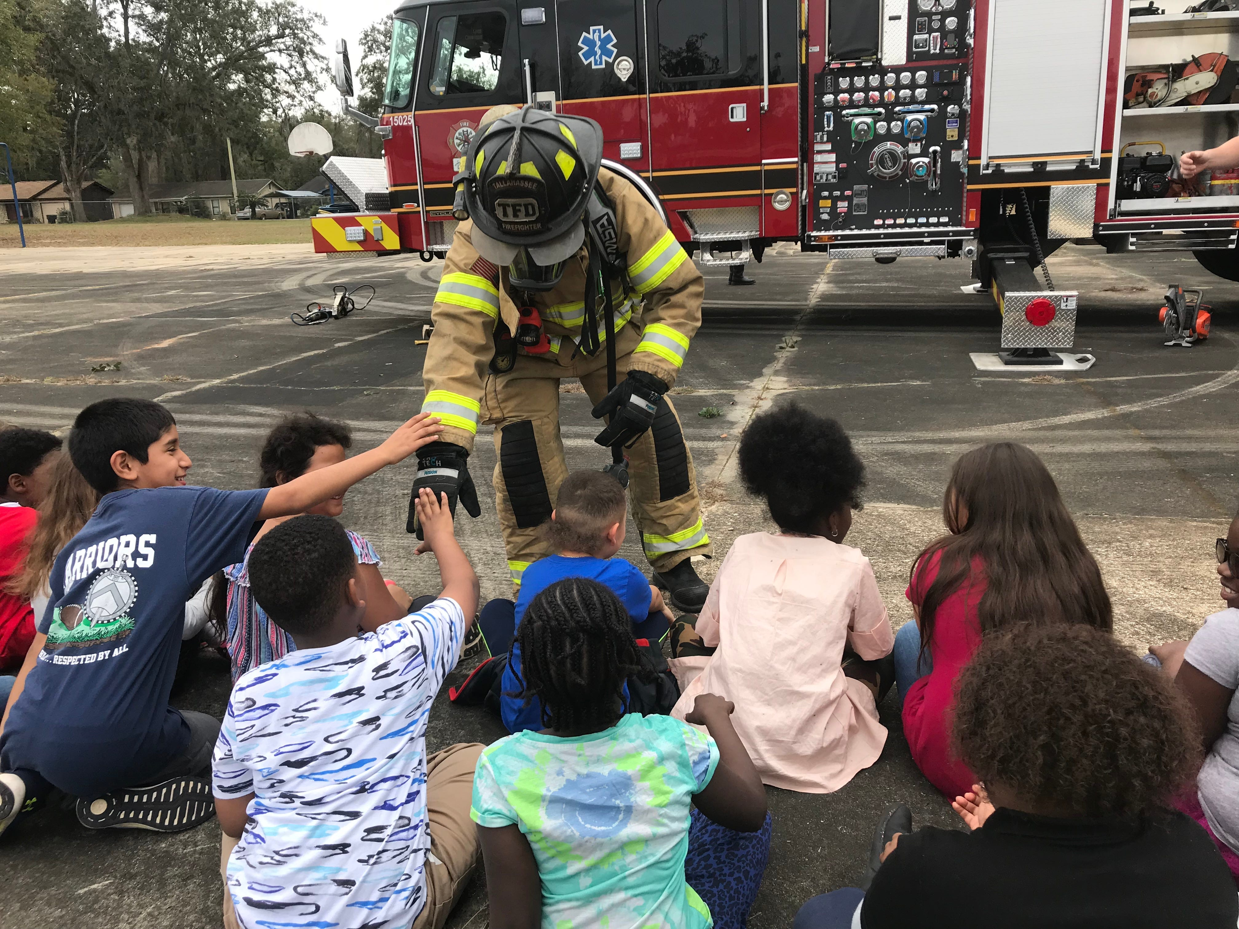 Engineer Jeff Brady lets Sabal Palm Elementary second graders feel his gloves while visiting the school Friday.
