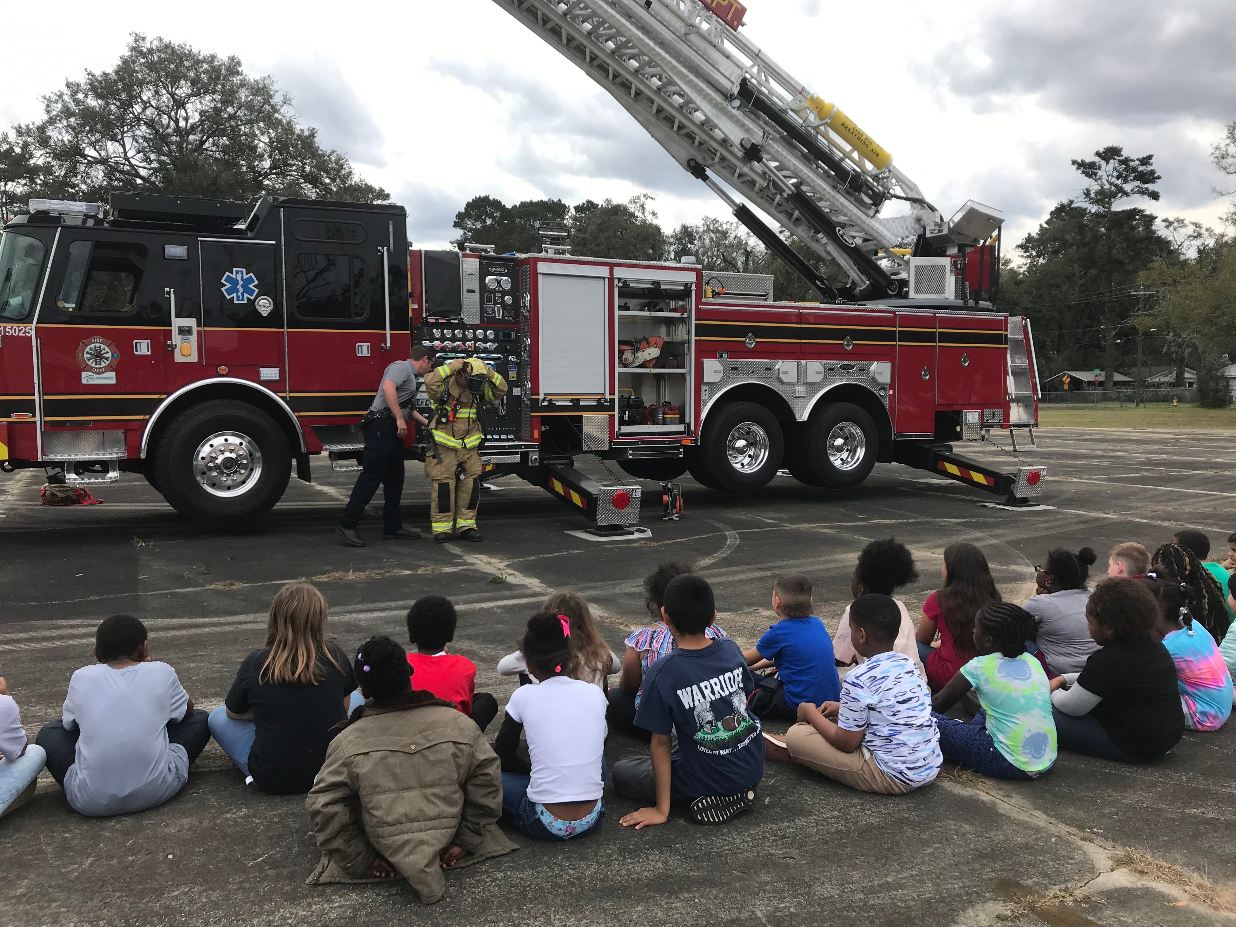 Firefighter Tom Burns, left, and Engineer Jeff Brady tell Sabal Palm second graders about fire safety and what firefighters do on Friday.