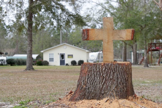 A cross carved in a tree stump in Bristol, Fla., Friday Feb. 15, 2019.