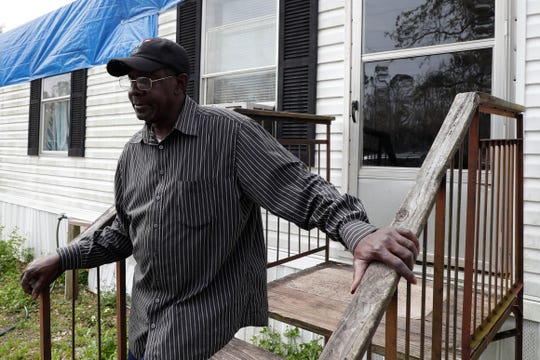 Kenny Bouie stands on the stairs outside of the trailer he rents in Bristol, Fla., Friday Feb. 15, 2019. Bouie's trailer had the roof torn apart by Hurricane Michael in Oct. 2018 and is still in need of being repaired.