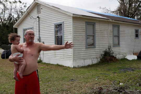 Bill Davis stands with his grandson Larry outside the home he rents in Bristol, Fla., Friday Feb. 15, 2019. Tarps cover the roof protecting the home from having further water damage first caused by Hurricane Michael in Oct. 2018.