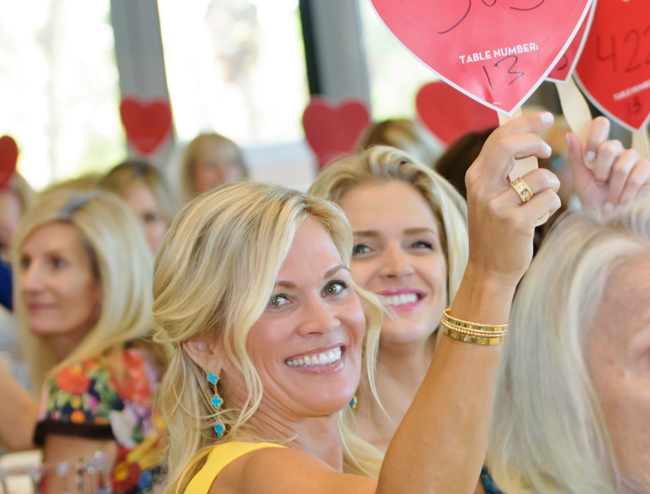 Alli Nicklaus raises her heart-shaped bid paddle at the Golden Heart Luncheon in Palm Beach Gardens.