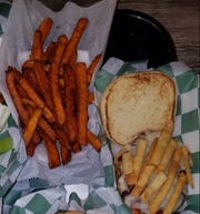 Grilled chicken sandwich topped with BBQ sauce, grilled onions, Monterrey jack cheese  and tortilla strips. Shown with a side order of sweet potato fries tossed in brown sugar and salt.