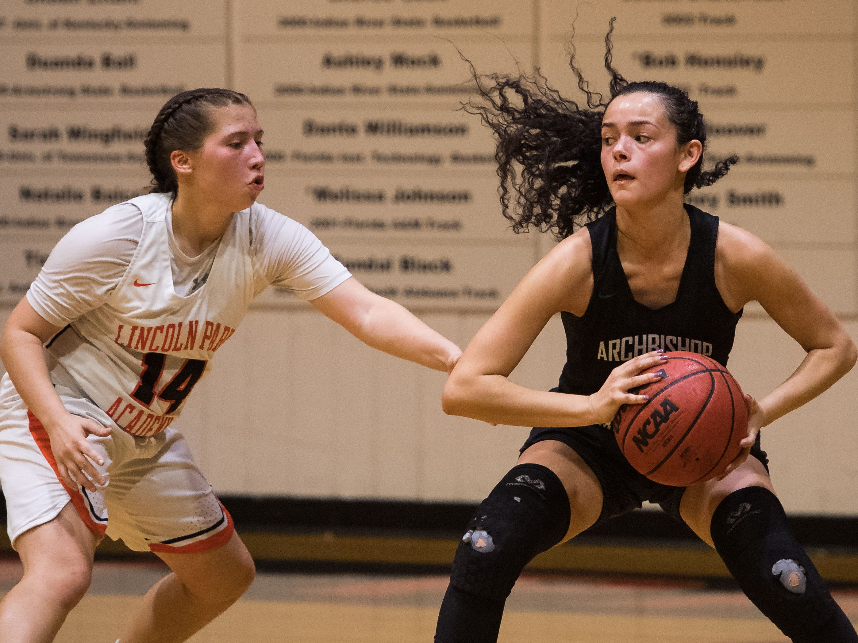 Lincoln Park Academy's Sophia Marrero (left) guards Archbishop McCarthy (Fort Lauderdale) player Vanessa Grimaldo closely during the fourth period of the high school girls basketball regional quarterfinal game Thursday, Feb. 14, 2019, Lincoln Park Academy in Fort Pierce.
