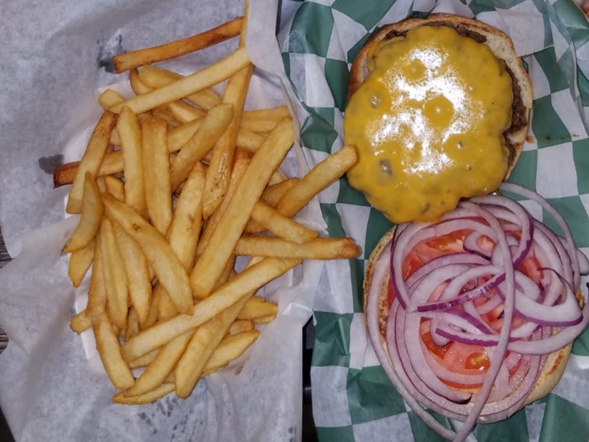 Joe Burger with an extra 1/4 pound patty, cheddar cheese, tomato, and raw onion. Shown with a side order of French fries.