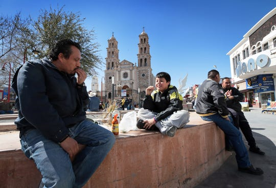 Rafael Jimenez has a snack with his son Rafael Jimenez Jr., 10, Tuesday, February, 12, 2019 at Plaza de Armas next to Juarez's downtown centerpiece, the Cathedral de Nuestra Senora de Guadalupe. Juarez had been held in the grips of violence and fear for years. Life is now returning to the streets.