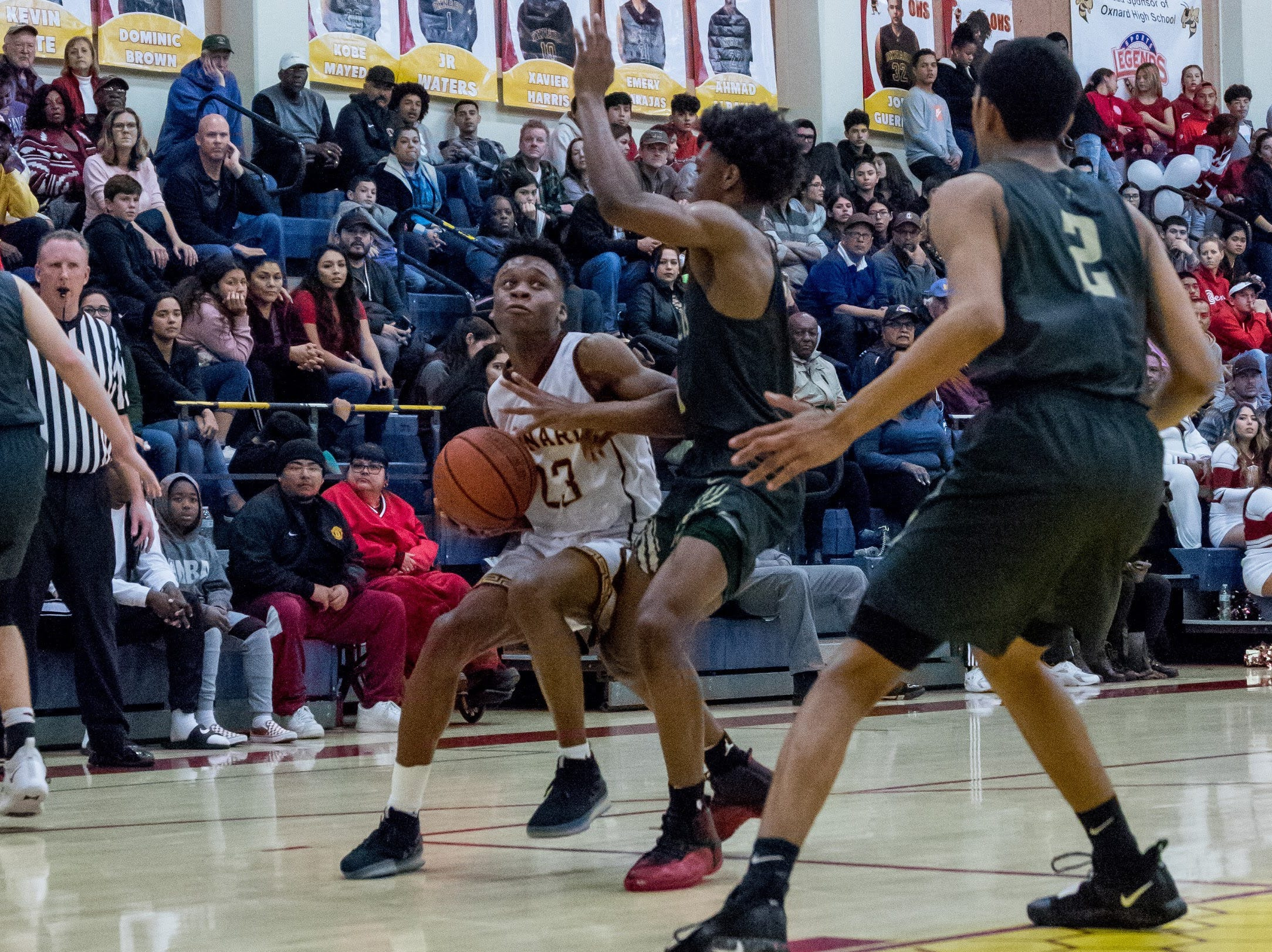 Oxnard's Stacy Johnson looks for room around St. Francis defenders during the Yellowjackets' 61-49 win in a Division 3AA quarterfinal Thursday night.