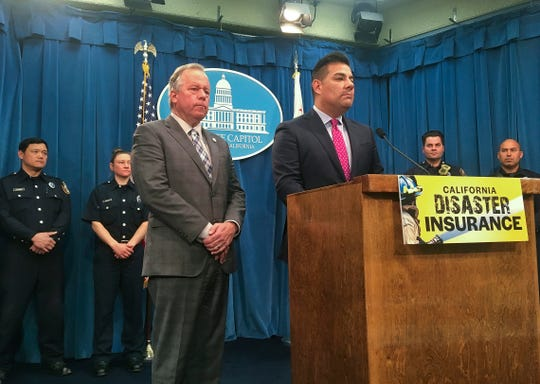 Democratic state Sen. Bill Dodd of Napa, left, and Insurance Commissioner Ricardo Lara, right, at the podium, speak at a news conference as Sacramento Fire Department firefighters stand behind them at the state Capitol on Thursday. Some state officials want California to take out insurance to help cover taxpayers' costs in bad wildfire seasons.