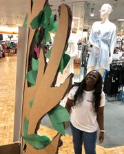 Chrysantate Pryor, lingerie sales department supervisor, looks over an Angel Tree in her department at Dillard's in Sikes Senter on Friday afternoon as she sets up for an event beginning this weekend. The store will be accepting donations to purchase bras for women staying at Faith Refuge.