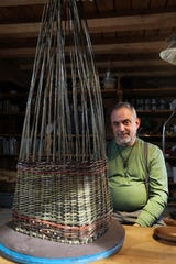 Howard Peller with an in-progress basket at his studio in Roseville. Peller grows the willows with which he weaves baskets.