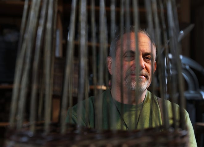 Howard Peller, the basket farmer, is seen through a basket be was weaving at his Roseville studio. Peller grows the willows he weaves the basket from and also builds living willow sculptures.