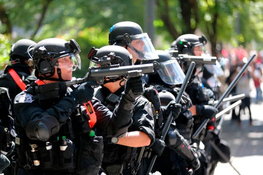 """Police prepare to push back against protesters on Aug. 4, 2018, in Portland, Oregon. Small scuffles broke out Saturday as police in Portland, Oregon, deployed """"flash bang"""" devices and other means to disperse hundreds of right-wing and self-described anti-fascist protesters."""