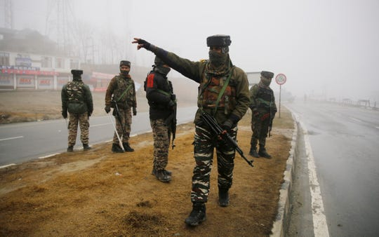 Indian security personnel stand guard at the blast site in Lethpora area of south Kashmir's Pulwama district, some 25 kilometers south of Srinagar, the summer capital of Indian Kashmir, 15 February 2019. At least 44 Indian paramilitary Central Reserve Police Force (CRPF) personnel were killed and several injured when a Jaish-e-Mohammed militant rammed an explosive-laden vehicle into a CRPF convoy along Srinagar-Jammu highway at Lethpora area in south Kashmir's Pulwama district on 14 February 2019, according local media reports.