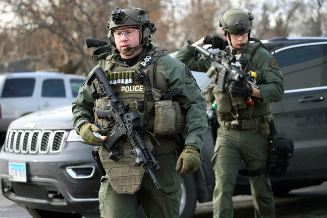 Law enforcement personnel gather near the scene where an active shooter was reported in Aurora, Ill., Friday, Feb. 15, 2019.