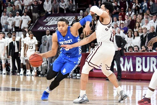 Kentucky guard Keldon Johnson handles the ball while being defended by Mississippi State guard Quinndary Weatherspoon.