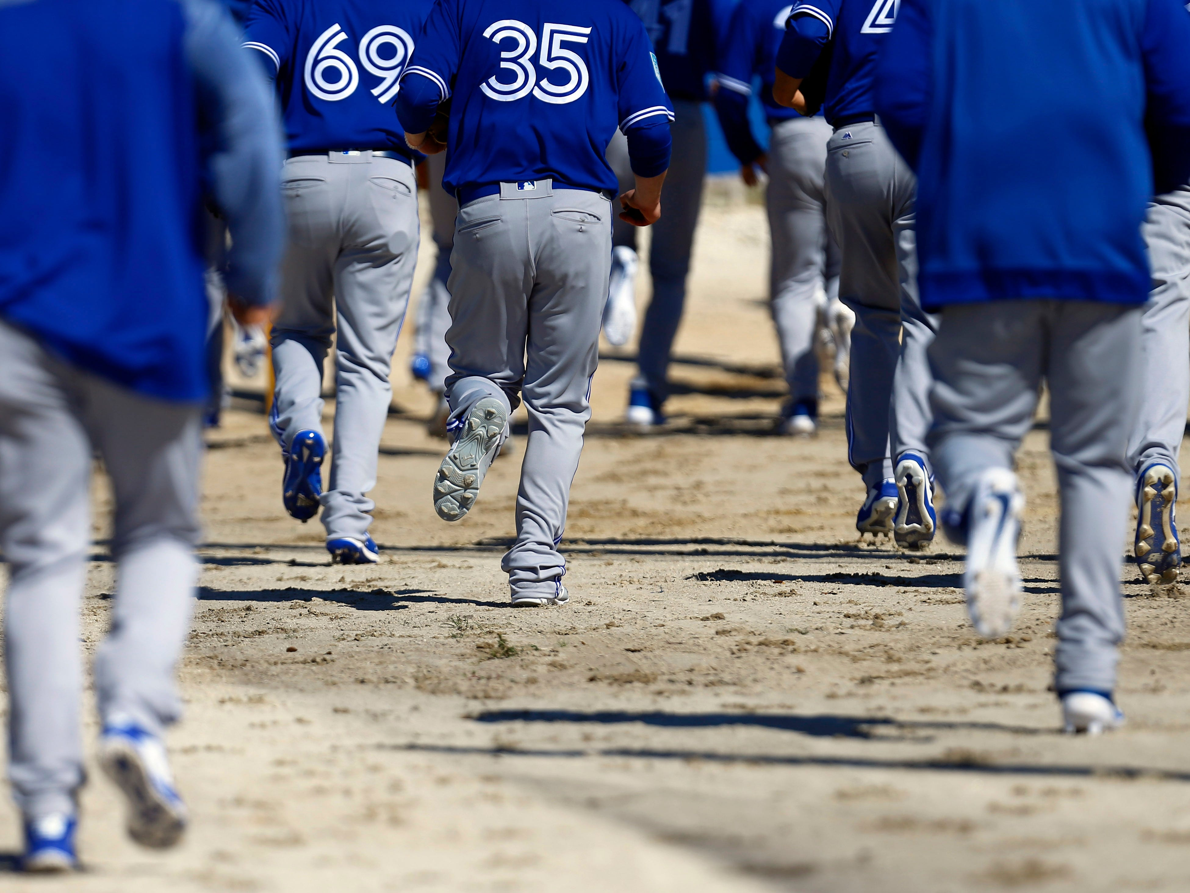 Feb. 14: Blue Jays players jog out to the practice fields.