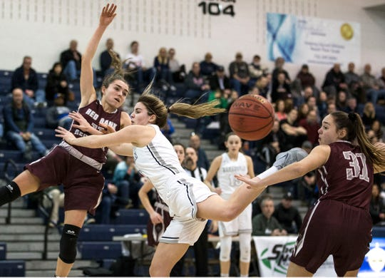 Shore Conference Tournament quarterfinals featuring Manasquan vs Red Bank Regional. Manasquan's Lola Mullaney goes to the hoop between Red Bank Regional's Meghan Murray and Emma Moriarity.Toms River, NJSaturday, February 16, 2019