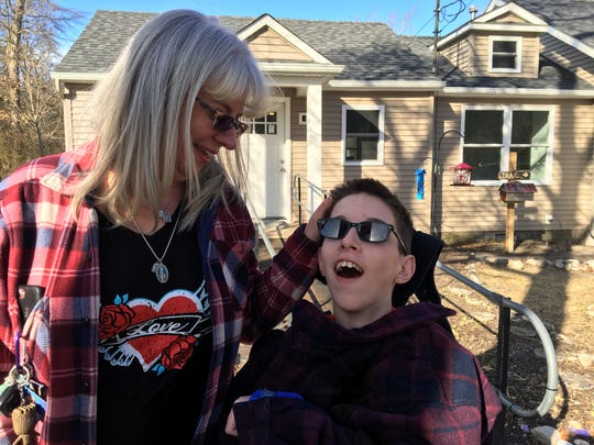 Kim Falzarano (left) with her son Val in front of their Bayville home.