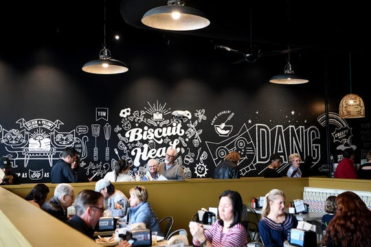 Patrons wait in line to order at the newly opened Biscuit Head South Asheville location on Hendersonville Road on Feb. 15, 2019. The new restaurant is the third Asheville location and features a half wall to separate the dining area from the line of people waiting to order.