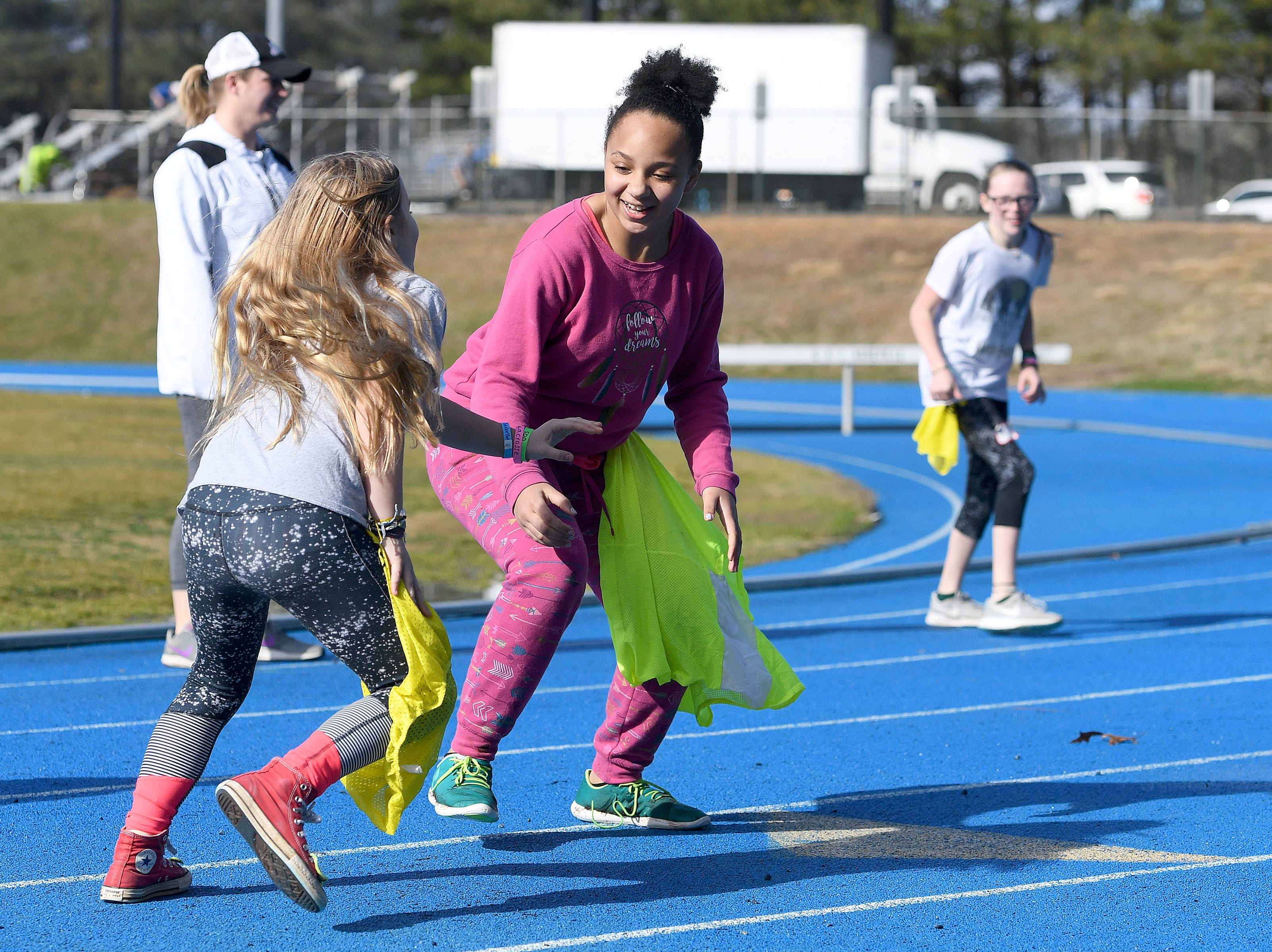 Julia Trollinger, 10, left, and Mary-Grayce Lee, 11, chase each other in a game of pinny tag during a lacrosse clinic at the National Girls and Women in Sports Day at UNC Asheville on Feb. 16, 2019. The clinic, hosted by Asheville Parks and Recreation and Buncombe County Recreation Services introduced girls to different sports of their choice throughout the morning.
