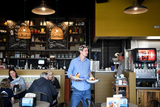 Mike Fisera carries food to a table at the newly opened Biscuit Head South Asheville location on Hendersonville Road on Feb. 15, 2019. The new restaurant in the third Asheville location.