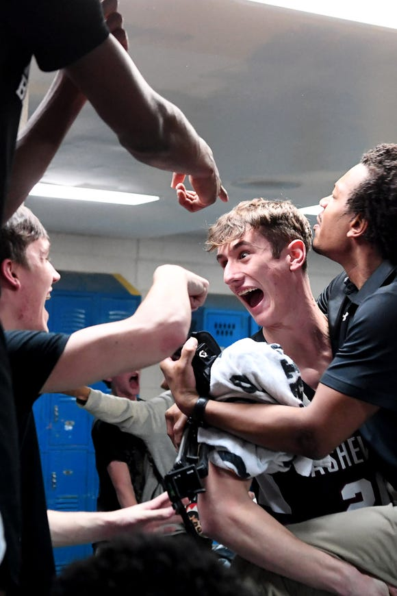 Asheville's Nico Horschman holds assistant coach Desmond McAfee as they celebrate their 76-59 win over West Henderson Feb. 15, 2019 in Hendersonville.