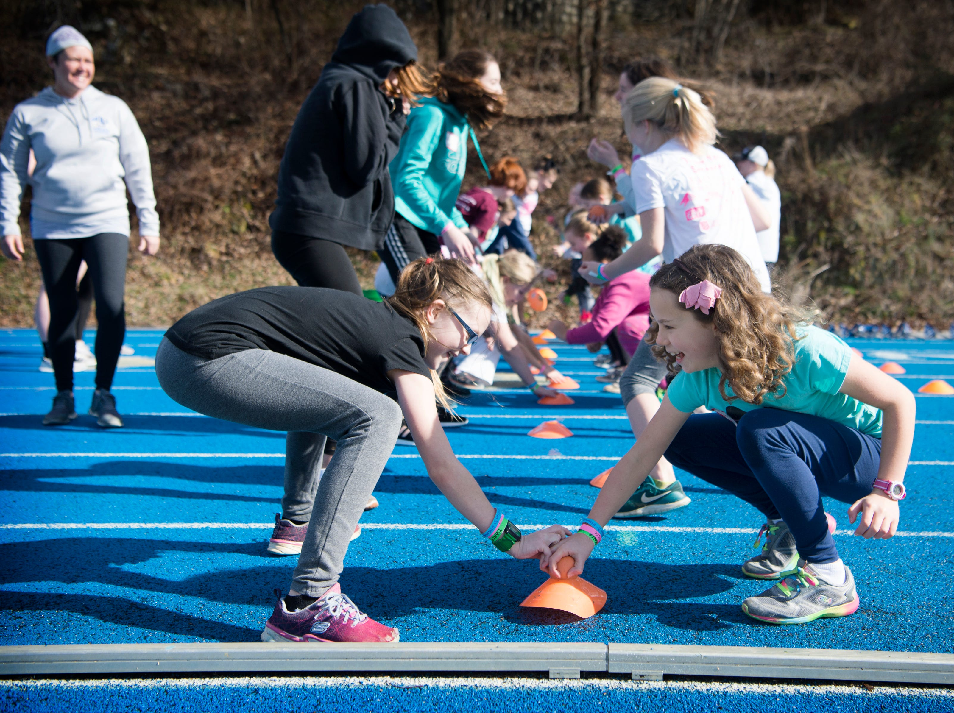 "Maryn Hester, 9, left, and Cadence Daly, 9, each reach for a lacrosse ball during a game of ""head, shoulders, knees and toes"" during a clinic at the National Girls and Women in Sports Day at UNC Asheville on Feb. 16, 2019. The clinic, hosted by Asheville Parks and Recreation and Buncombe County Recreation Services introduced girls to different sports of their choice throughout the morning."