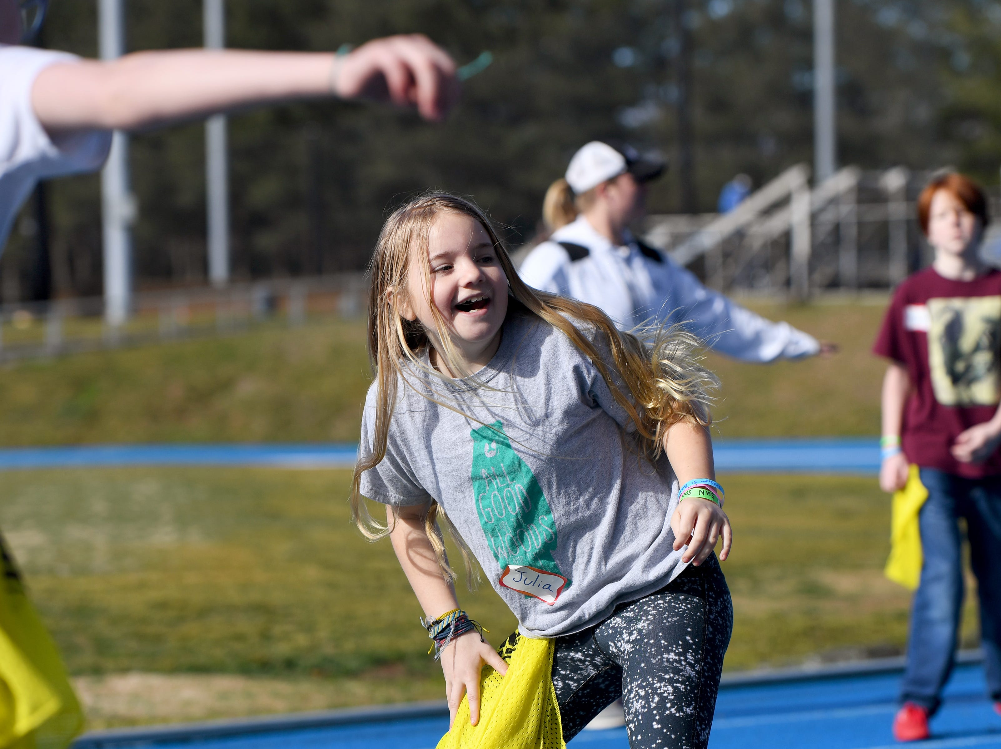 Julia Trollinger, 10, laughs as she plays a game of pinny tag during a lacrosse clinic at the National Girls and Women in Sports Day at UNC Asheville on Feb. 16, 2019. The clinic, hosted by Asheville Parks and Recreation and Buncombe County Recreation Services introduced girls to different sports of their choice throughout the morning.
