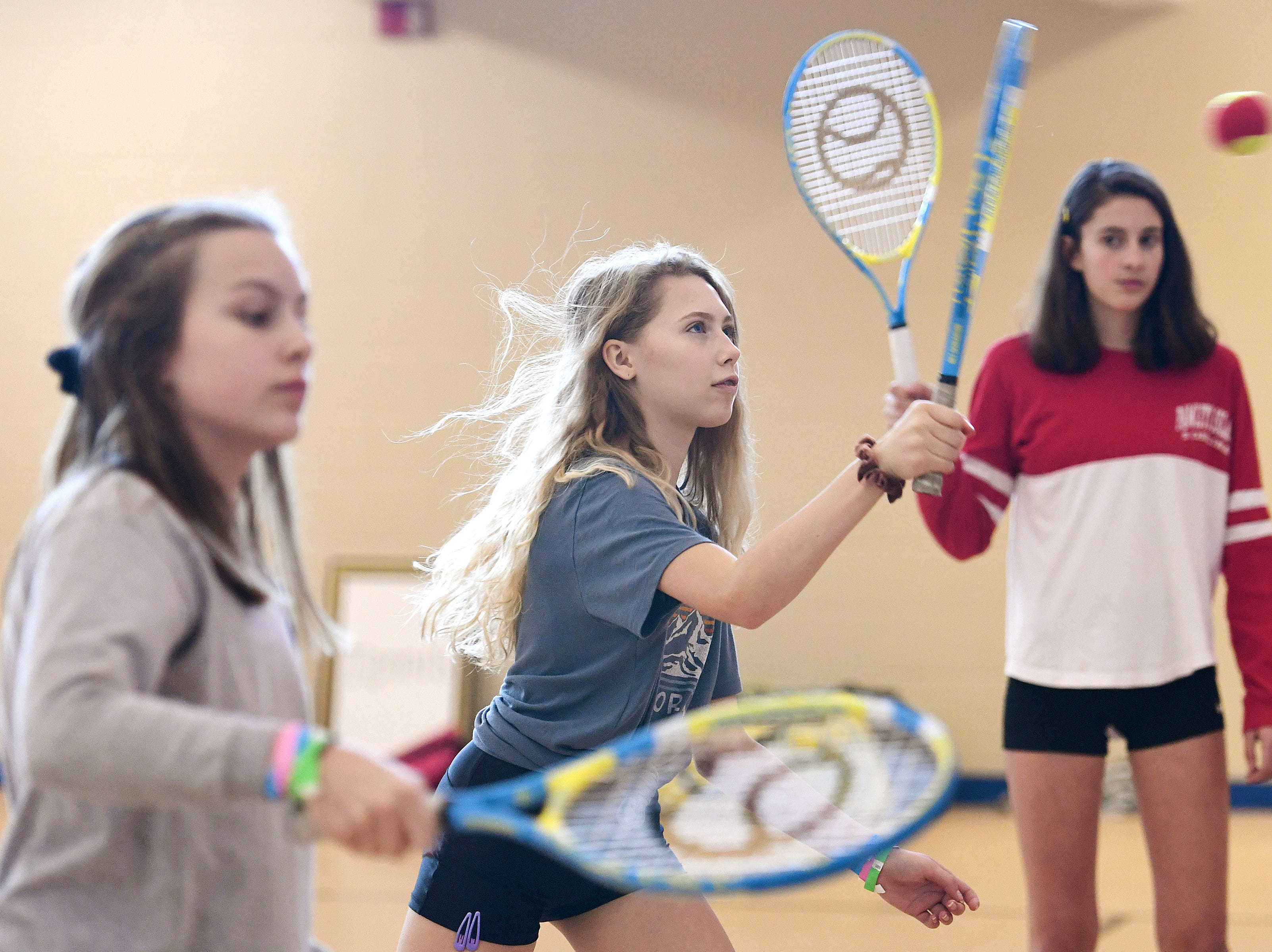 From left: Isabelle Kelley, 13, Maya Hannon, 13, and Ramona Eldridge, 14, work on returning tennis balls during a clinic at the National Girls and Women in Sports Day at UNC Asheville on Feb. 16, 2019. The clinic, hosted by Asheville Parks and Recreation and Buncombe County Recreation Services introduced girls to different sports of their choice throughout the morning.