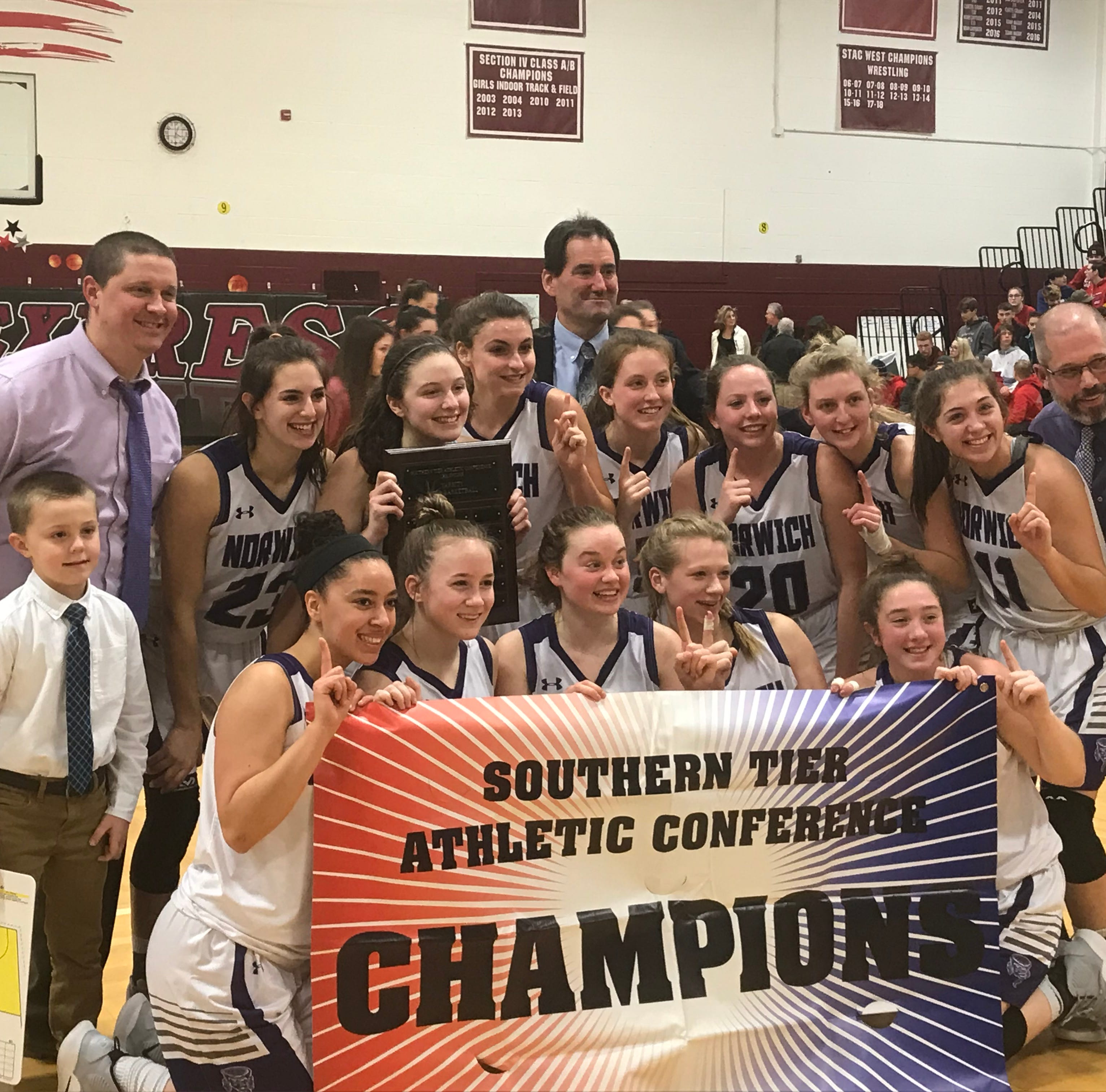 Norwich's girls basketball team celebrates its first Southern Tier Athletic Conference title since 2001 after a 74-39 victory over Owego on Friday at Elmira High.
