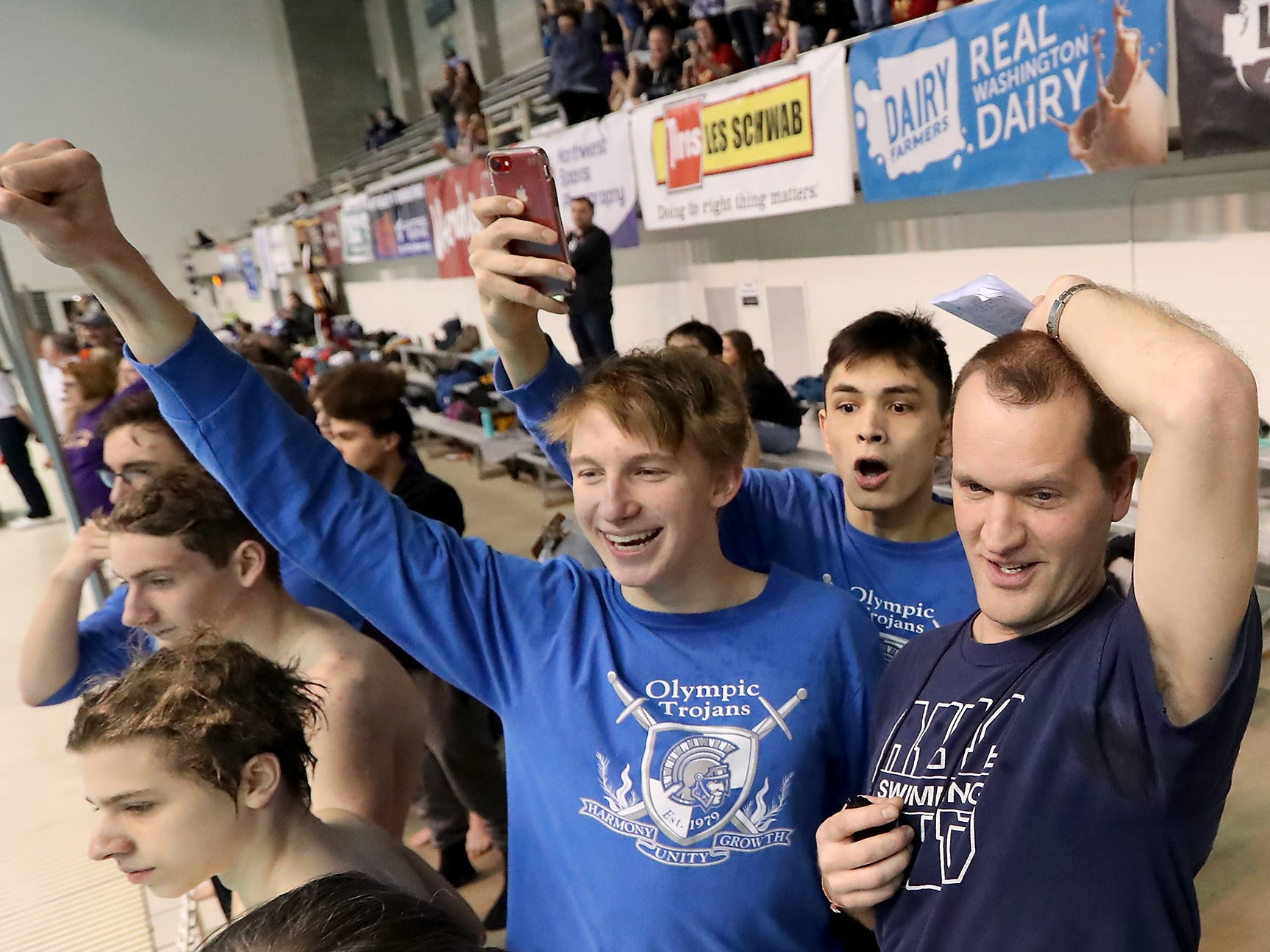 Olympic swimmer Rainer Meyer (left) Tiernann Shelton and coach Paul Henderson cheer on their 400 freestyle relay as they cling to first place at the state swim meet Saturday.