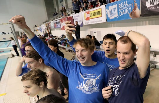 Olympic swimmer Rainer Meyer (left), Tiernann Shelton and coach Paul Henderson cheer during the Trojans' winning performance at the state swim and dive championships in February.