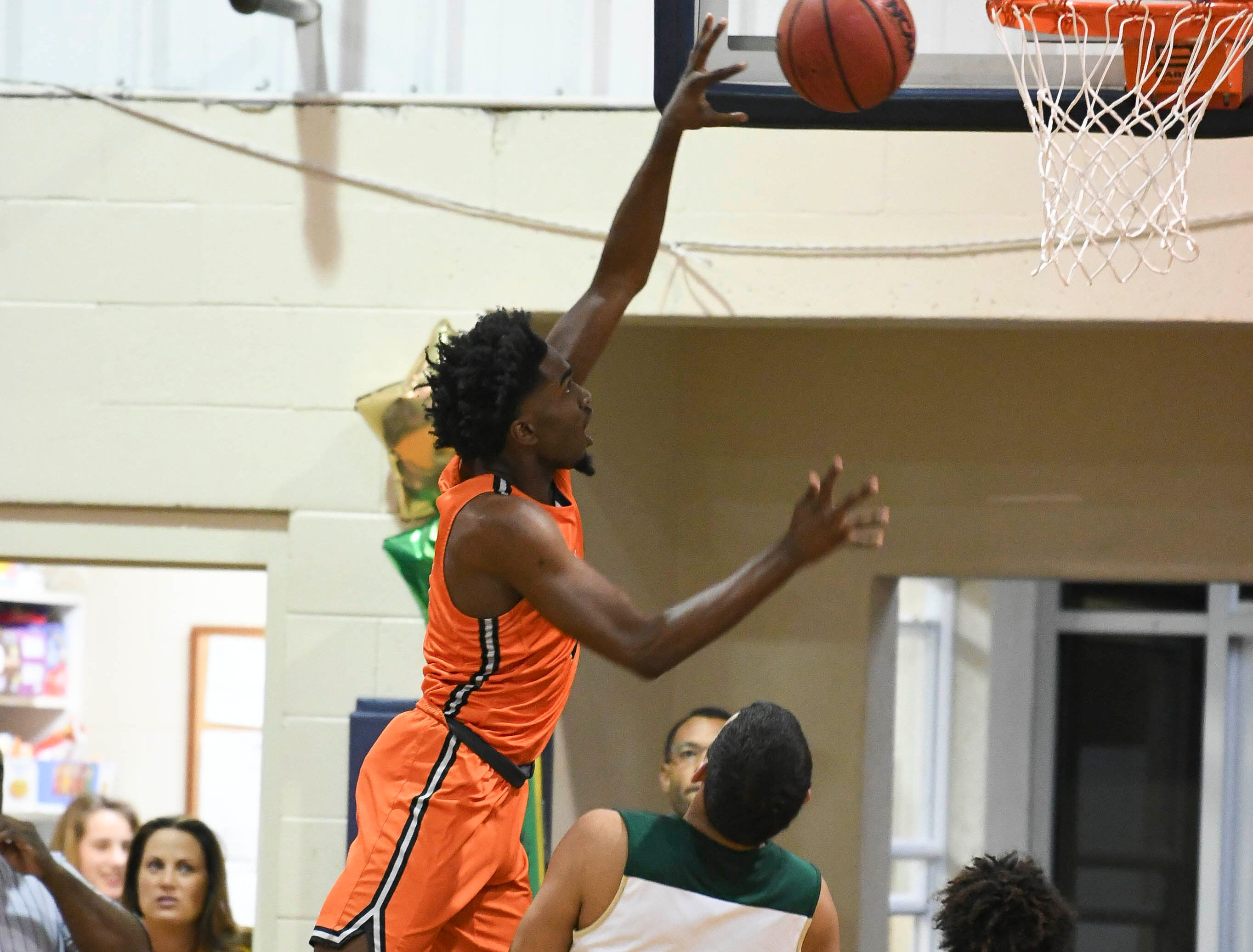 Cocoa's Marquise Freeman takes the ball to the basket over MCC defenders Favian Galindo (22) and Tyler Robinson during Friday's District 7-5A boys basketball championship game at Holy Trinity in Melbourne.