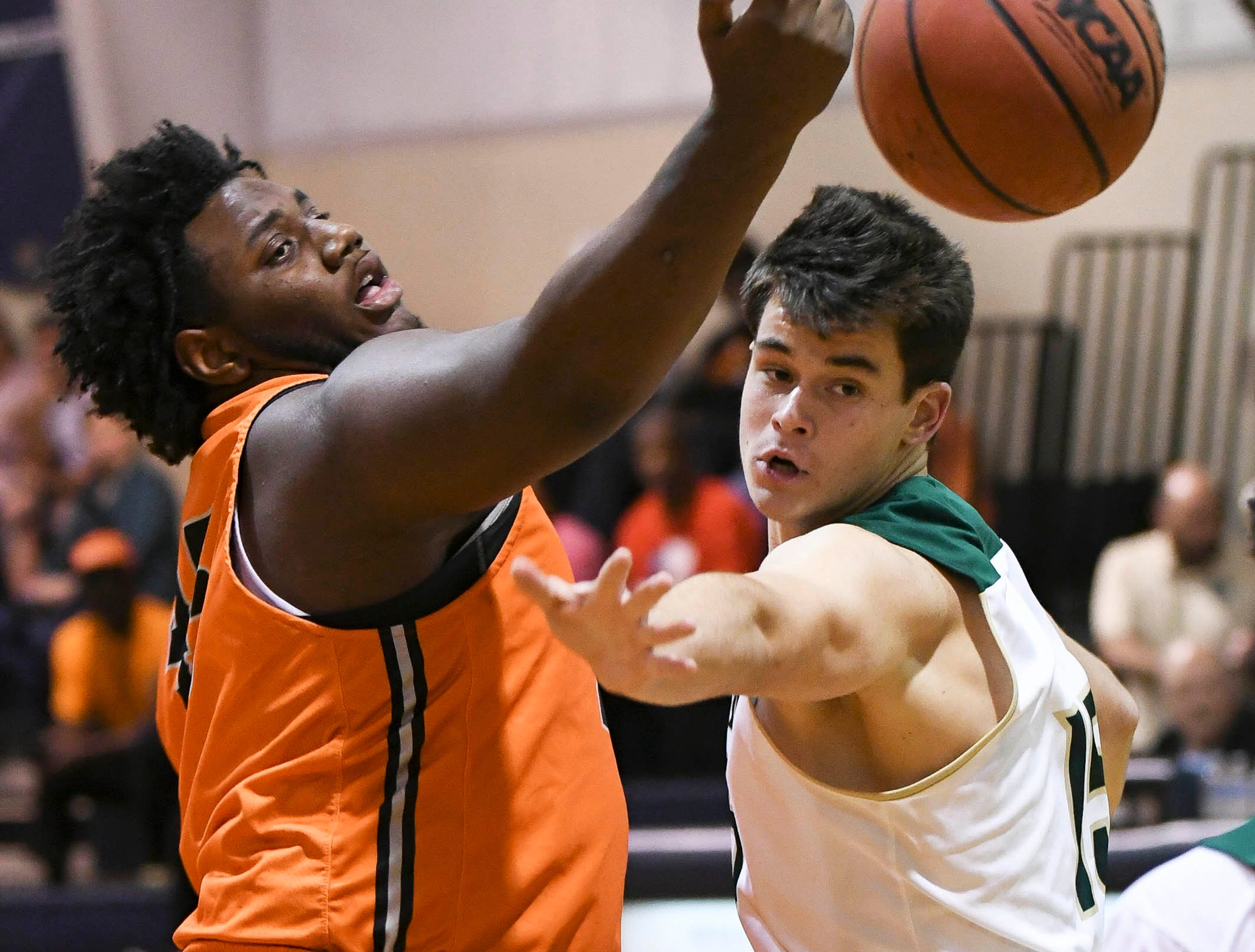 Richie Leonard of Cocoa and Milsey Goodwin of Melbourne Central Catholic fight for a rebound during District 7-5A boys basketball championship game at Holy Trinity in Melbourne