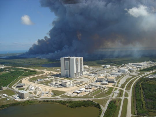 In this file photo by the U.S. Fish and Wildlife Service Fire Management Division, a previous prescribed fire is seen near the Vehicle Assembly Building at Kennedy Space Center.