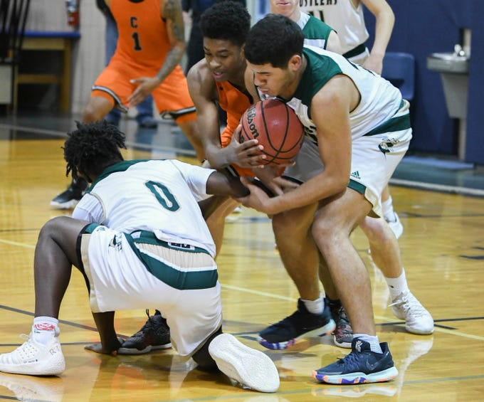 Cocoa's Jamariyae Robinson fights for a loose ball with De'Andre Cofield and Favian Galindo (22) during Friday's District 7-5A boys basketball championship game at Holy Trinity in Melbourne