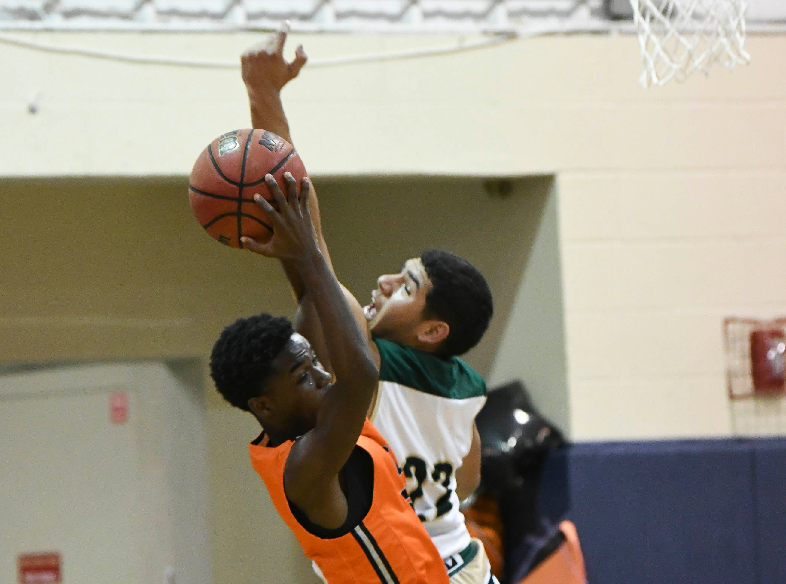 Cocoa's Samarion Bryant takes a rebound away from Favian Galindo of Melbourne Central Catholic during Friday's District 7-5A boys basketball championship game at Holy Trinity in Melbourne