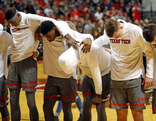 Texas Tech players stand by Norense Odiase, bent over, before an NCAA college basketball game against Baylor, Saturday, Feb. 16, 2019, in Lubbock, Texas. Two of Odiase's cousins died in a car accident Friday morning. (AP Photo/Brad Tollefson)