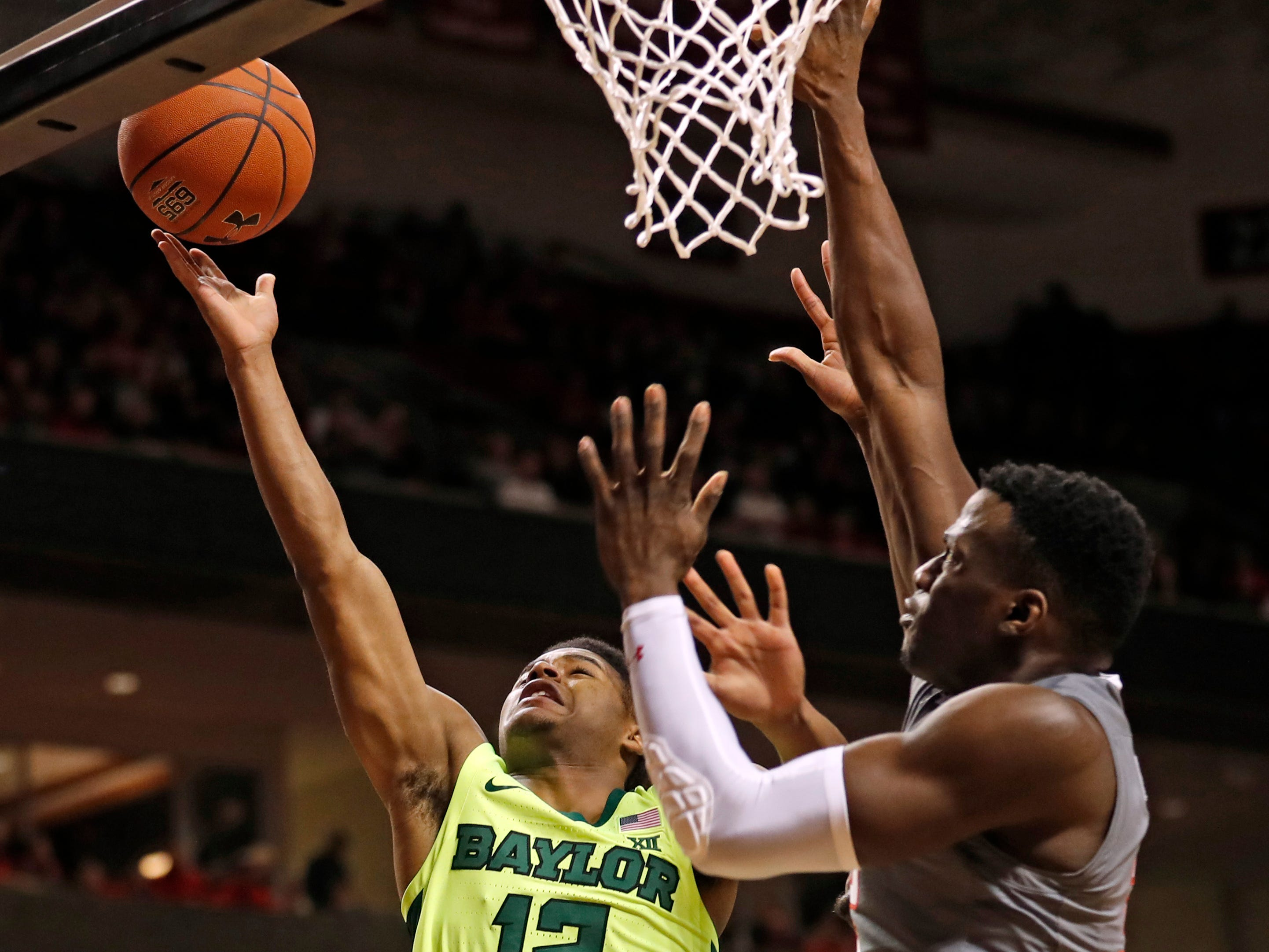 Baylor's Jared Butler (12) lays up the ball around Texas Tech's Norense Odiase (32) during the first half of an NCAA college basketball game Saturday, Feb. 16, 2019, in Lubbock, Texas. (AP Photo/Brad Tollefson)