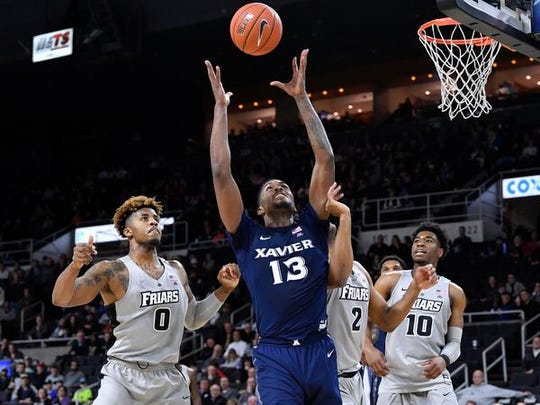 Xavier Musketeers forward Naji Marshall (13) rebounds the ball in front of Providence Friars center Nate Watson (0) and guard A.J. Reeves (10) Saturday during the second half at the Dunkin Donuts Center.