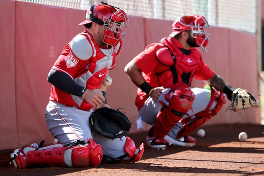 Cincinnati Reds catcher Kyle Farmer (52) blocks a pitch during catching drills, Saturday, Feb. 16, 2019, at the Cincinnati Reds spring training facility in Goodyear, Arizona.