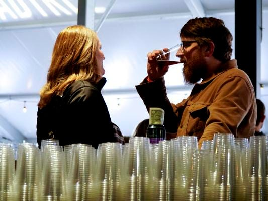 """We try to support everyone,"" said Doug Camfield, right, a brewer at Warped Wing Brewing Company. Brew crews from Yellow Springs Brewery and The Common Beer Company were also attended MadTree Brewing's Winter Bonanza, Feb. 19, 2019."