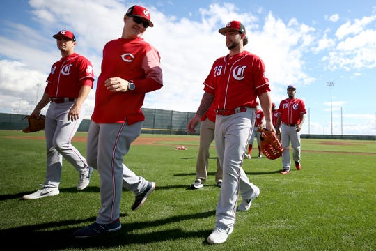 Cincinnati Reds manager David Bell (25), center, turns back to talk to pitcher Brandon Finnegan (29), right, between drills, Saturday, Feb. 16, 2019, at the Cincinnati Reds spring training facility in Goodyear, Arizona.