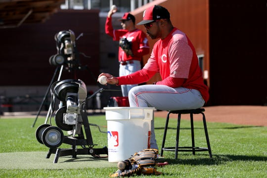 Former Cincinnati Reds player and special assistant Barry Larkin feeds a pitching machine during catching drills, Saturday, Feb. 16, 2019, at the Cincinnati Reds spring training facility in Goodyear, Arizona.