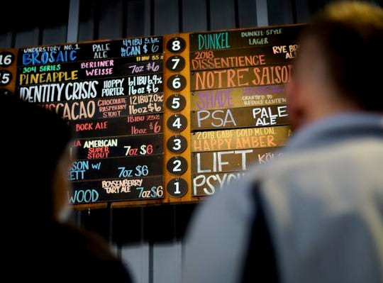 Attendees survey MadTree Brewing's lengthy beer list at Winter Bonanza, Feb. 19, 2019.