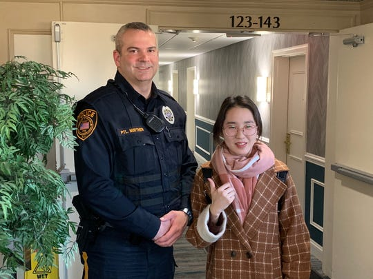 Feranklin Township Police Officer Patrick Nurthen with a Chinese woman who reported a theft in the township.