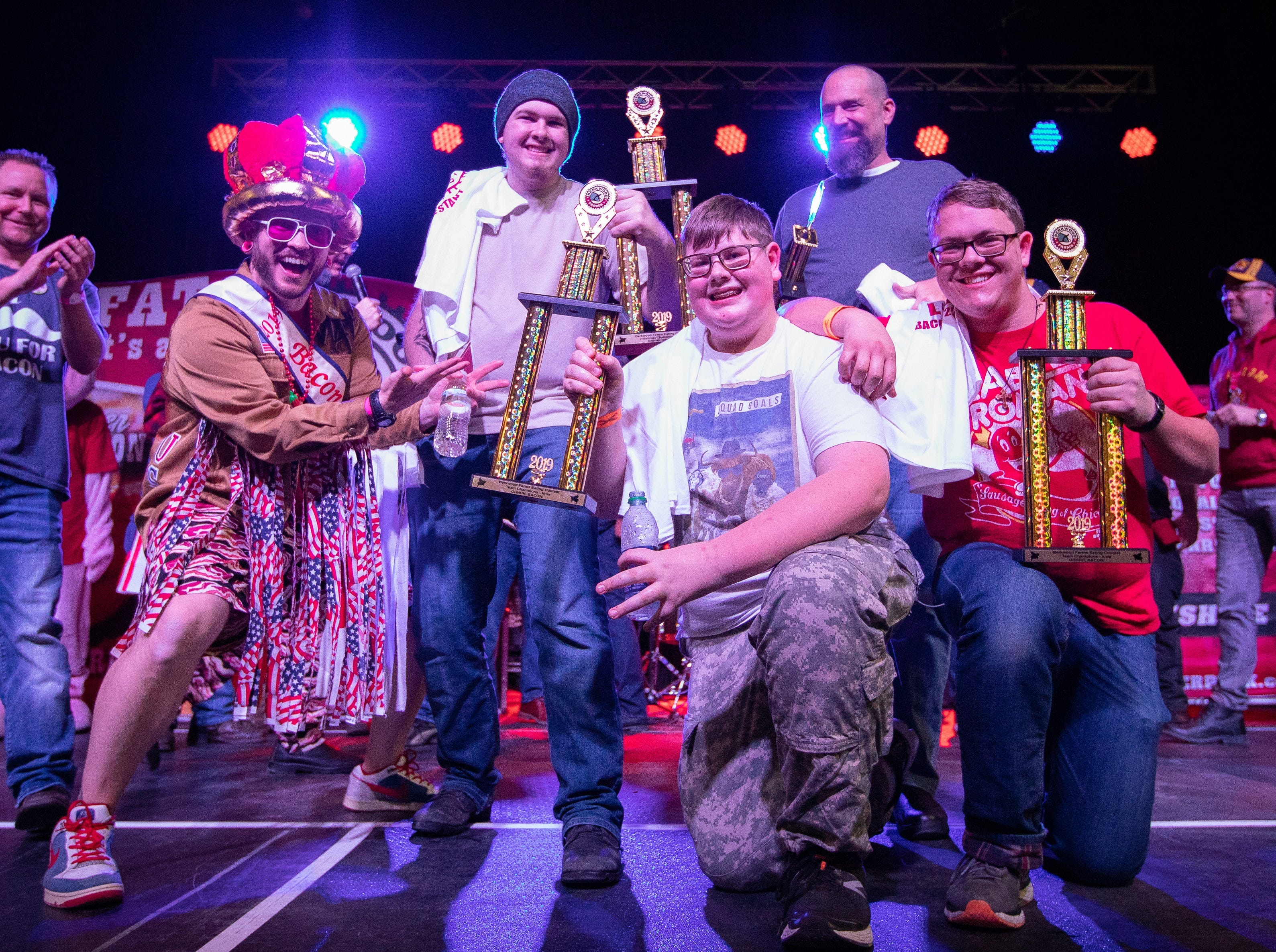 Bacon King Matt Weis (left) poses for a photo with Coleman Farrell, Ronan Farrell, Aarron Canino, and Kilian Farrell celebrate after they won the eating contest during the Bacon Fest at Hy-Vee Hall on Feb. 16, 2019 in Des Moines, Iowa.