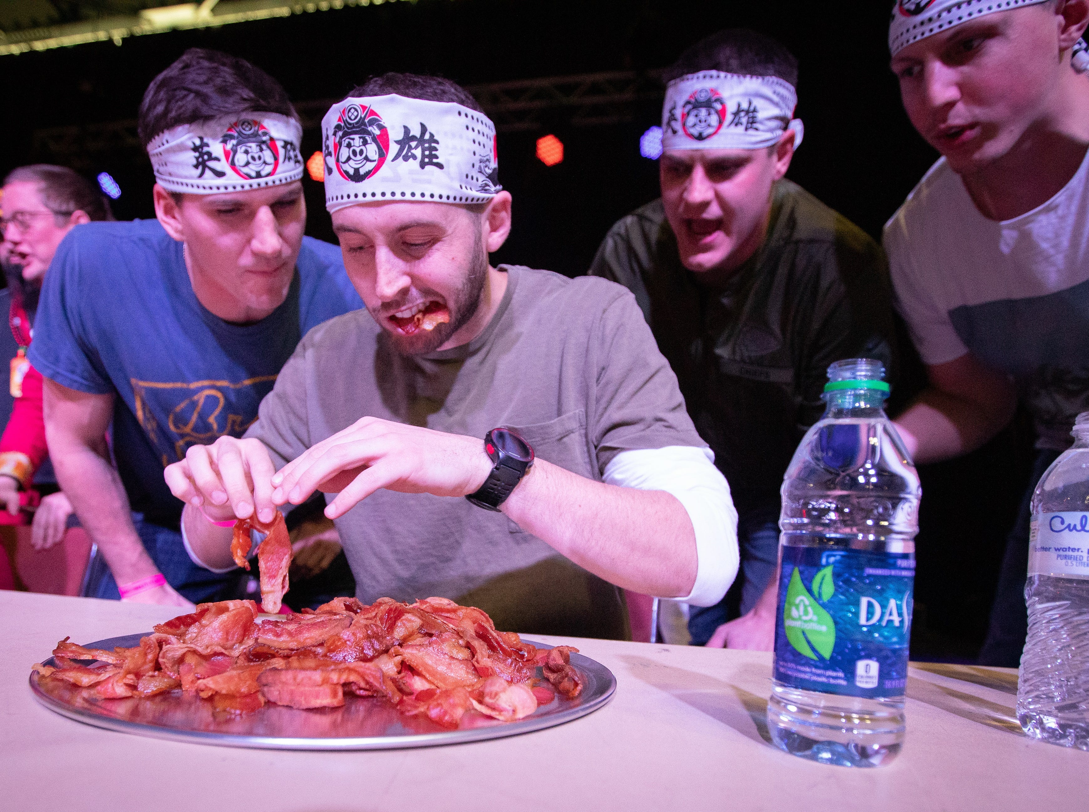 James Grunert, of Des Moines, participates in the eating contest as his teammates support him during the Bacon Fest at Hy-Vee Hall on Feb. 16, 2019 in Des Moines, Iowa.