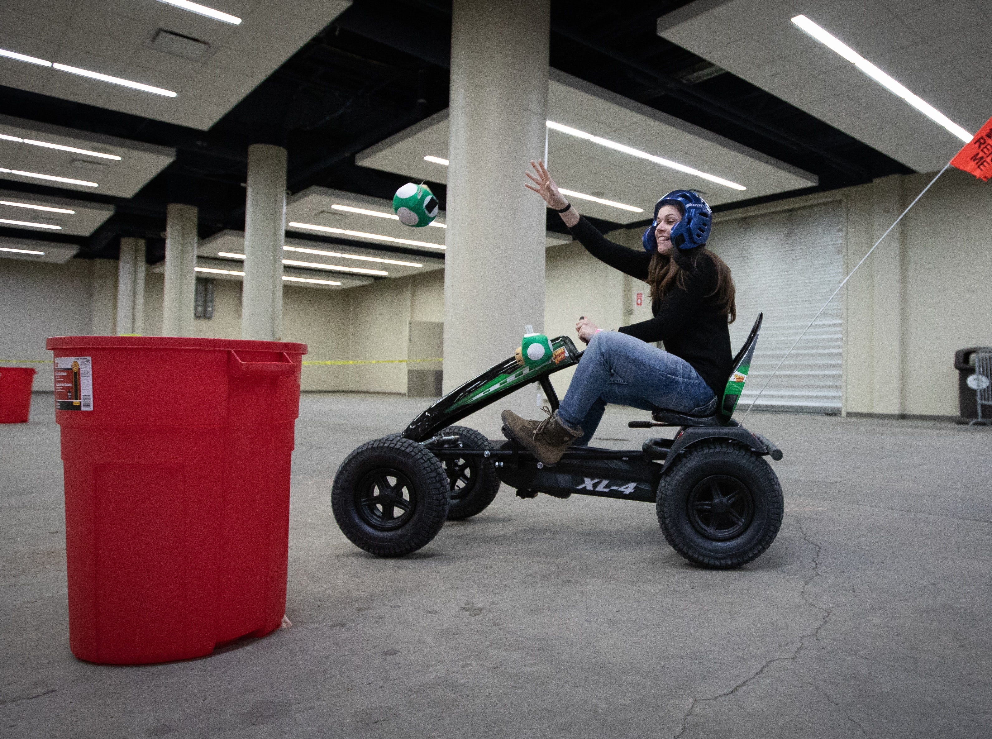 Sarah Gray, of Clive, throws a toy into a trash can during a go-kart race during the Bacon Fest at Hy-Vee Hall on Feb. 16, 2019 in Des Moines, Iowa.